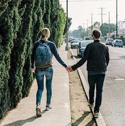 A picture of a man and woman holding hands while walking