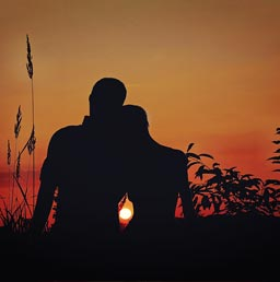 A silhouette of a lovely couple enjoying a beautiful sunset